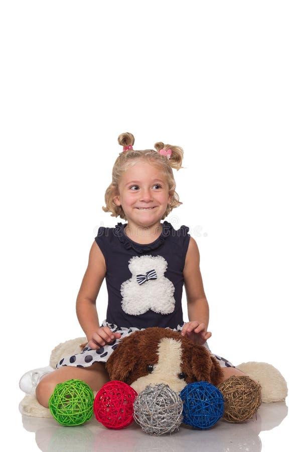 Menina loura pequena bonito que senta-se em um cão macio grande fotos de stock royalty free