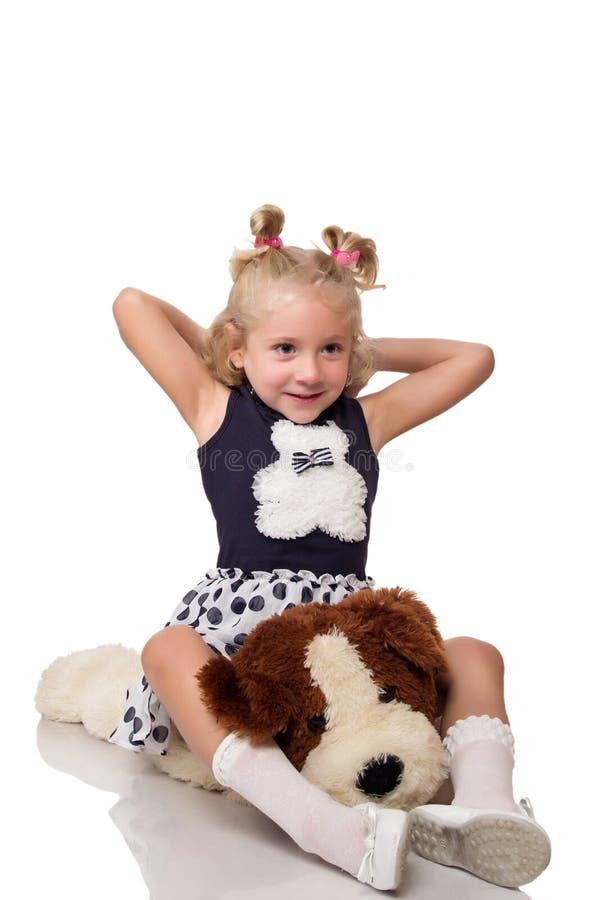 Menina loura pequena bonito que senta-se em um cão macio grande imagem de stock