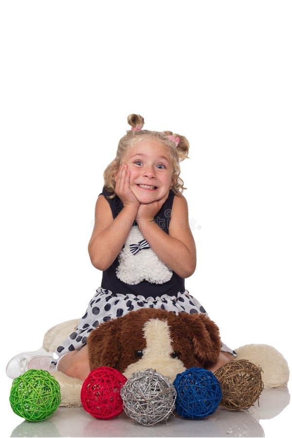 Menina loura pequena bonito que senta-se em um cão macio grande imagem de stock royalty free