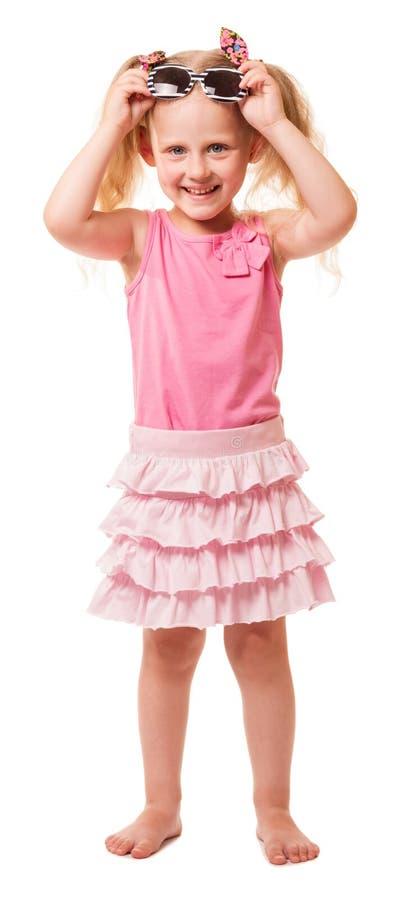 A menina loura pequena bonito veste os óculos de sol isolados no branco foto de stock royalty free