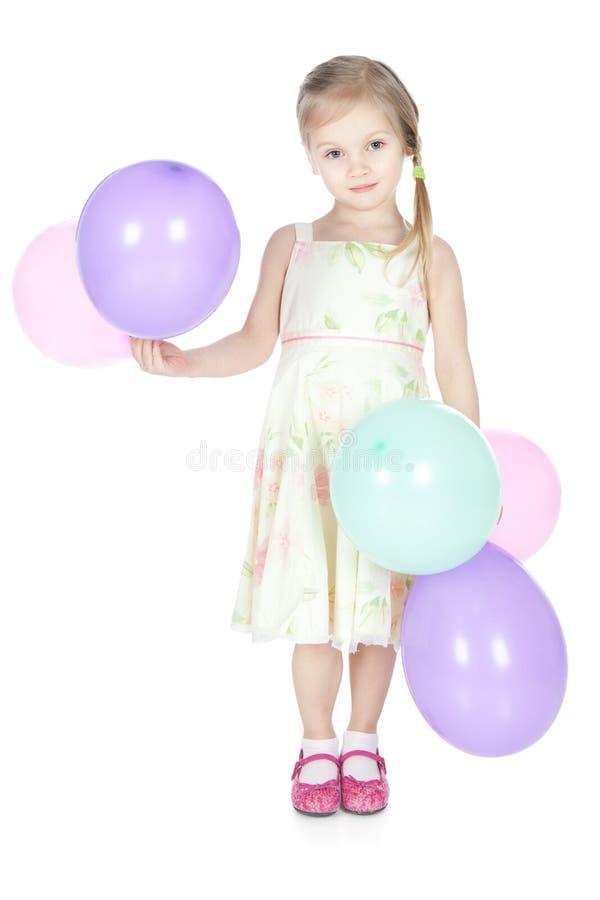 Menina loura pequena com os balões no estúdio imagem de stock royalty free