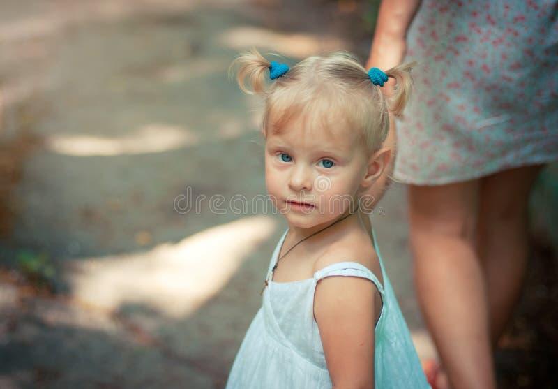 Menina loura pequena com os olhos azuis que guardam sua mão do ` s da mãe foto de stock