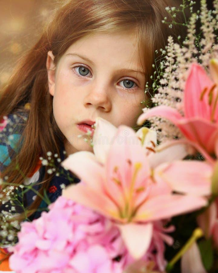 Menina loura pequena com ramalhete do lírio imagens de stock