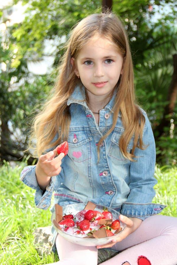 Menina loura pequena com uma placa de morangos frescas no verão imagem de stock royalty free