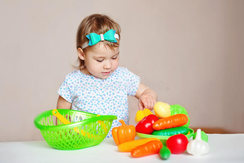 Menina loura pequena encantador em um vestido branco do verão, sentando-se na tabela e nos jogos com brinquedos plásticos imagens de stock royalty free
