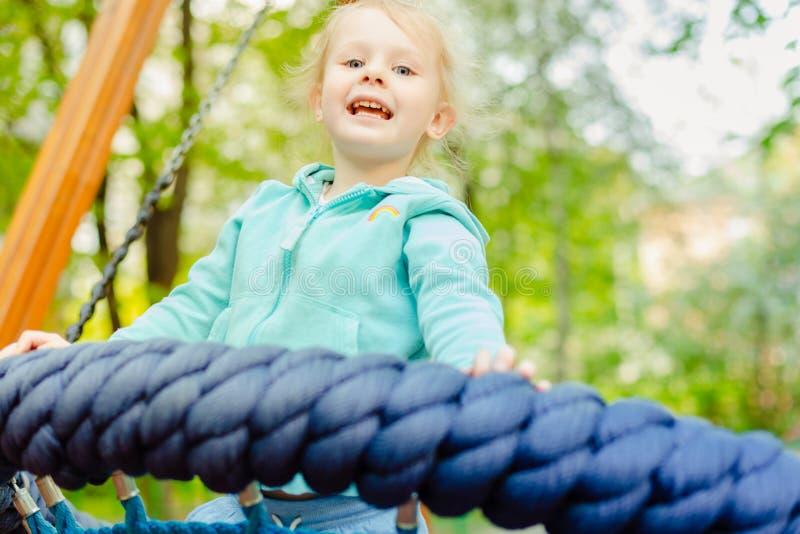 Menina loura pequena feliz que tem o divertimento em um campo de jogos imagens de stock royalty free