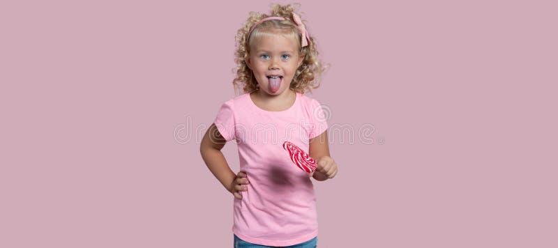 A menina loura pequena guarda o pirulito e mostra um tong isolado sobre o fundo cor-de-rosa fotos de stock royalty free