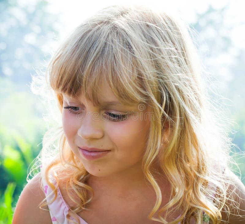 Menina loura pequena ligeiramente de sorriso imagem de stock