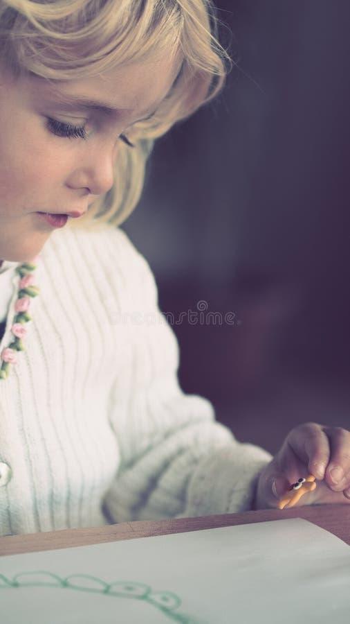 Menina loura pequena loura que faz o artcraft imagens de stock royalty free