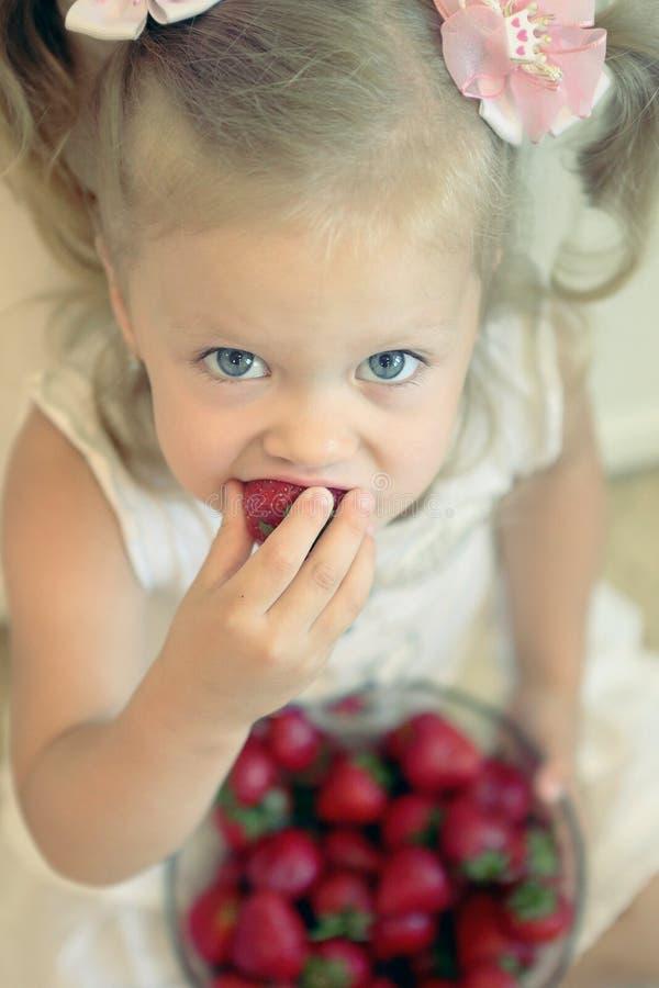 Menina loura pequena que come a morango foto de stock