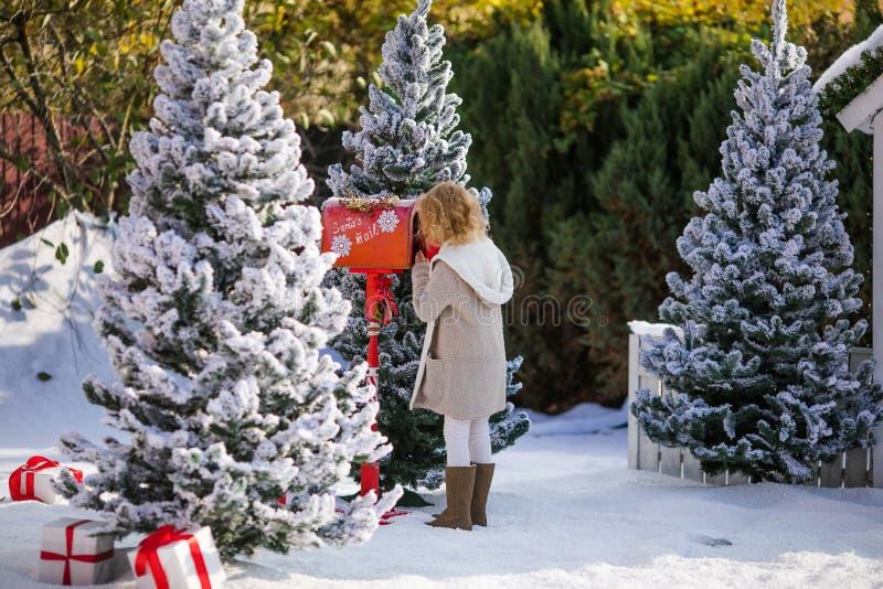 Menina loura pequena que envia sua carta com o wishlist a Santa, tempo do Natal imagem de stock
