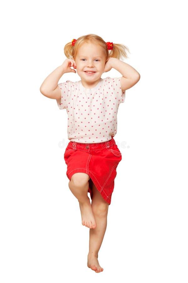 Menina loura pequena que sorri e que dança. foto de stock
