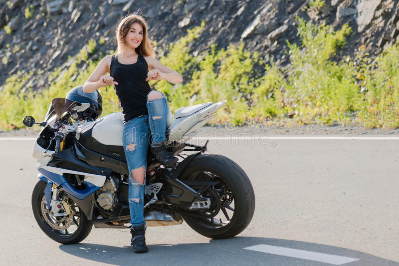 Menina loura perto da motocicleta moderna imagens de stock royalty free