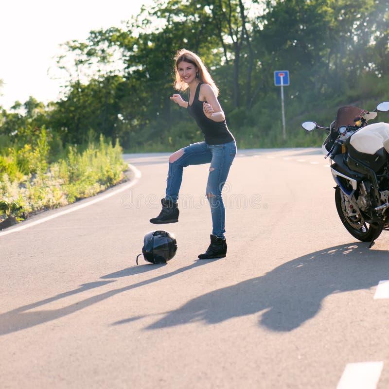 Menina loura perto da motocicleta moderna fotos de stock royalty free