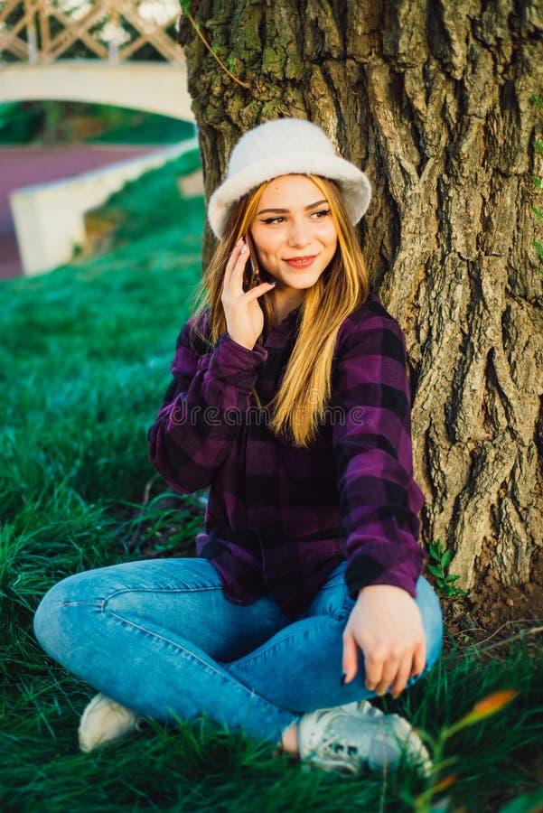 Menina loura perto de uma árvore que fala no telefone imagem de stock