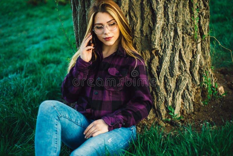 Menina loura perto de uma árvore que fala no telefone fotos de stock