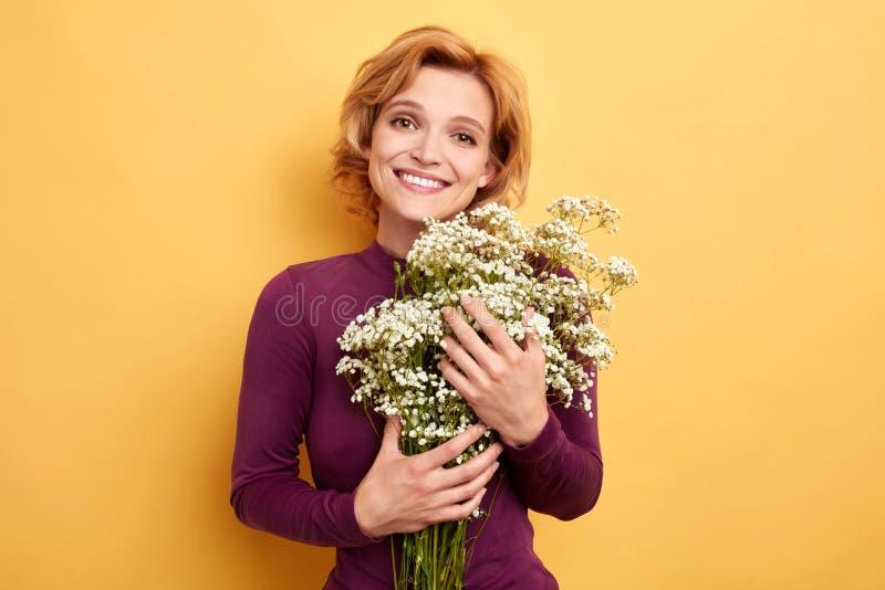Menina loura positiva alegre bonita que aprecia suas flores imagem de stock royalty free
