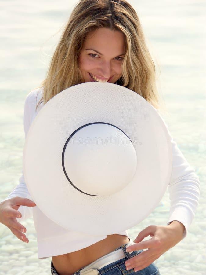 Menina loura que come o chapéu branco fotografia de stock