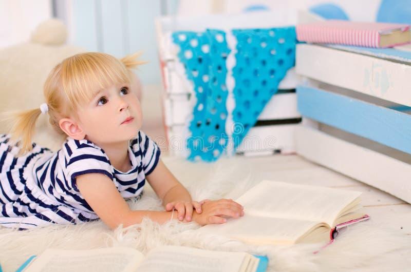 menina loura que encontra-se no assoalho com livros imagem de stock royalty free