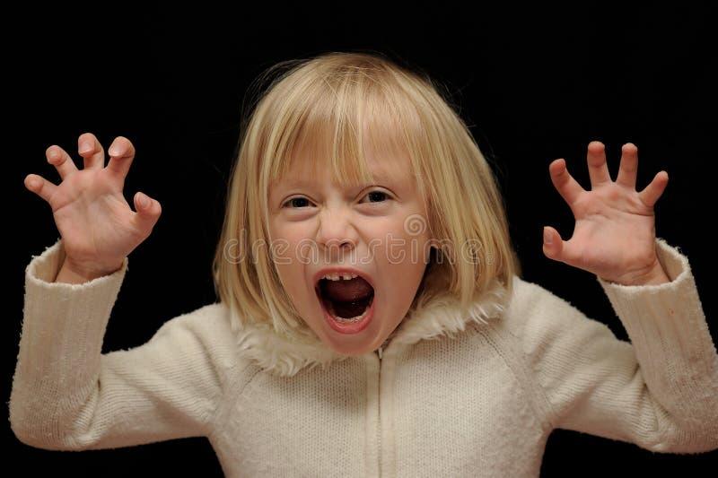 Menina loura que faz a face assustador foto de stock