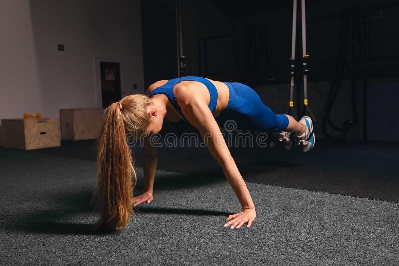 Menina loura que faz a imprensa acima dos exercícios no gym fotos de stock