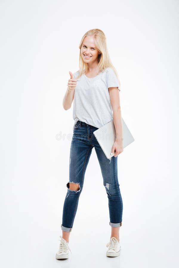 Menina loura que guarda um portátil e que dá o polegar acima do gesto imagem de stock