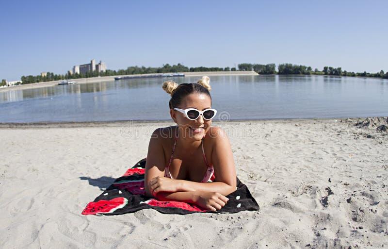 Menina loura que levanta na areia em um roupa de banho do biquini fotografia de stock royalty free