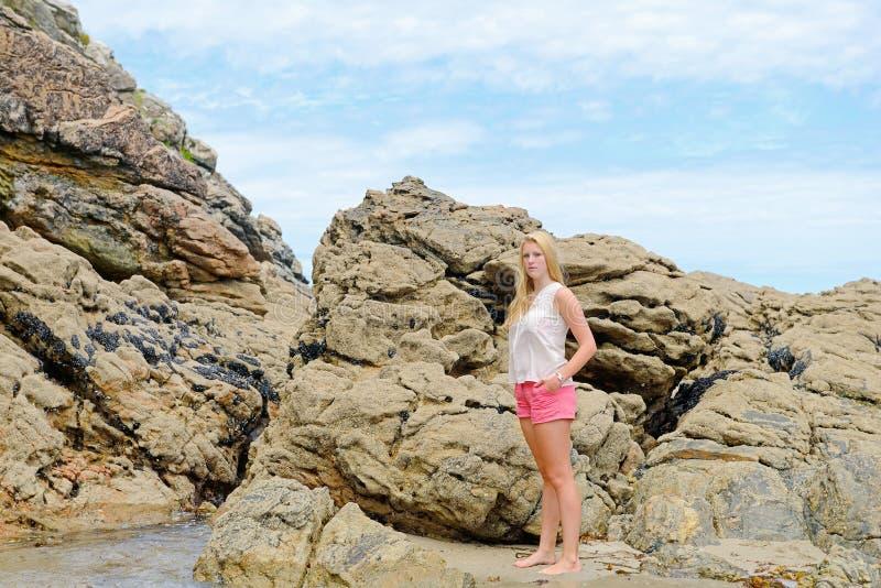 Menina loura que levanta na praia em Spain fotografia de stock