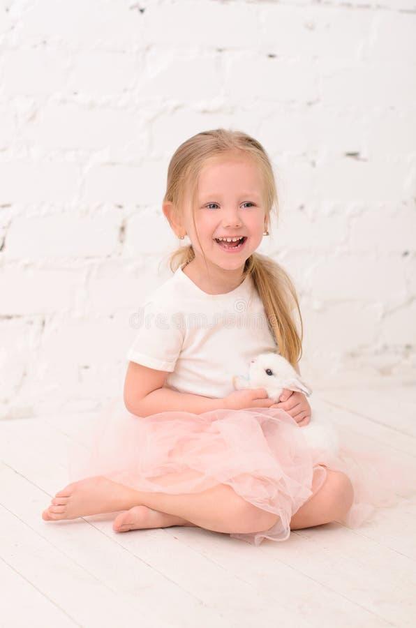 menina loura que senta-se com coelho imagens de stock