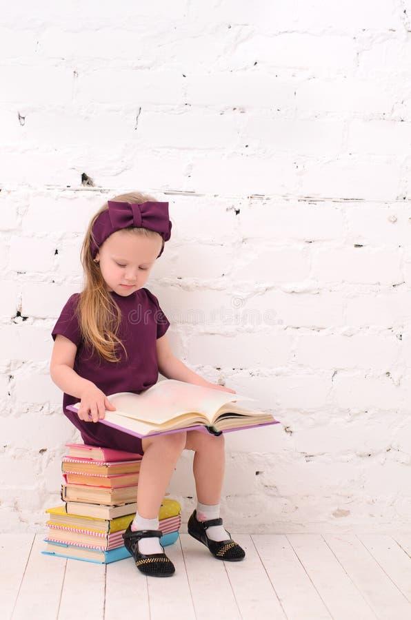 menina loura que senta-se em uma pilha dos livros imagens de stock royalty free
