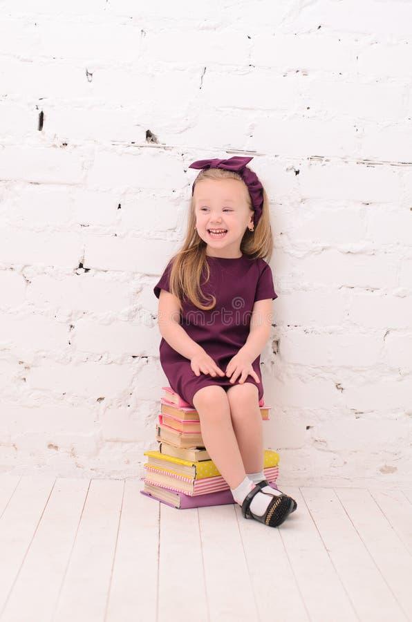 menina loura que senta-se em uma pilha dos livros foto de stock