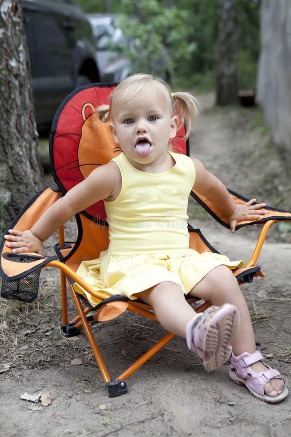 Menina loura que senta-se na cadeira foto de stock