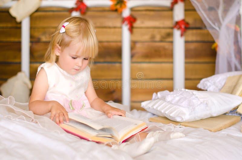 menina loura que senta-se na cama com um livro imagem de stock
