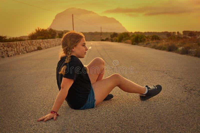 Menina loura que senta-se na estrada com Montgo imagens de stock