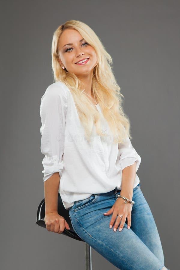 Menina loura que senta-se nas calças de brim vestindo da cadeira e na camisa branca imagem de stock royalty free