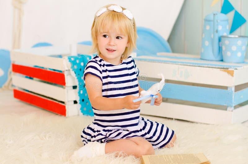 menina loura que senta-se no assoalho com um brinquedo fotos de stock royalty free