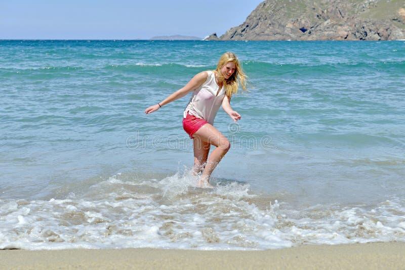 Menina loura que tem o divertimento na praia fotografia de stock