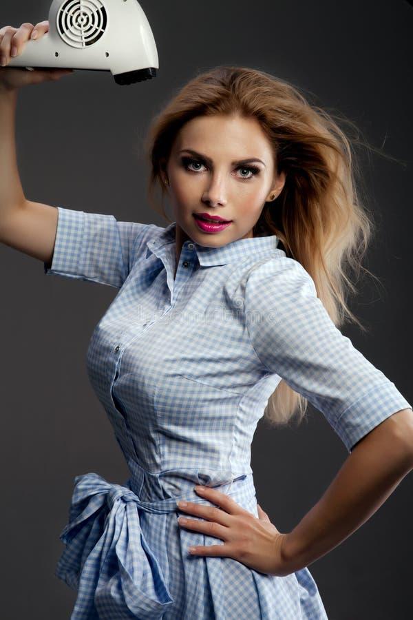 Menina loura que usa o secador de cabelo fotos de stock royalty free