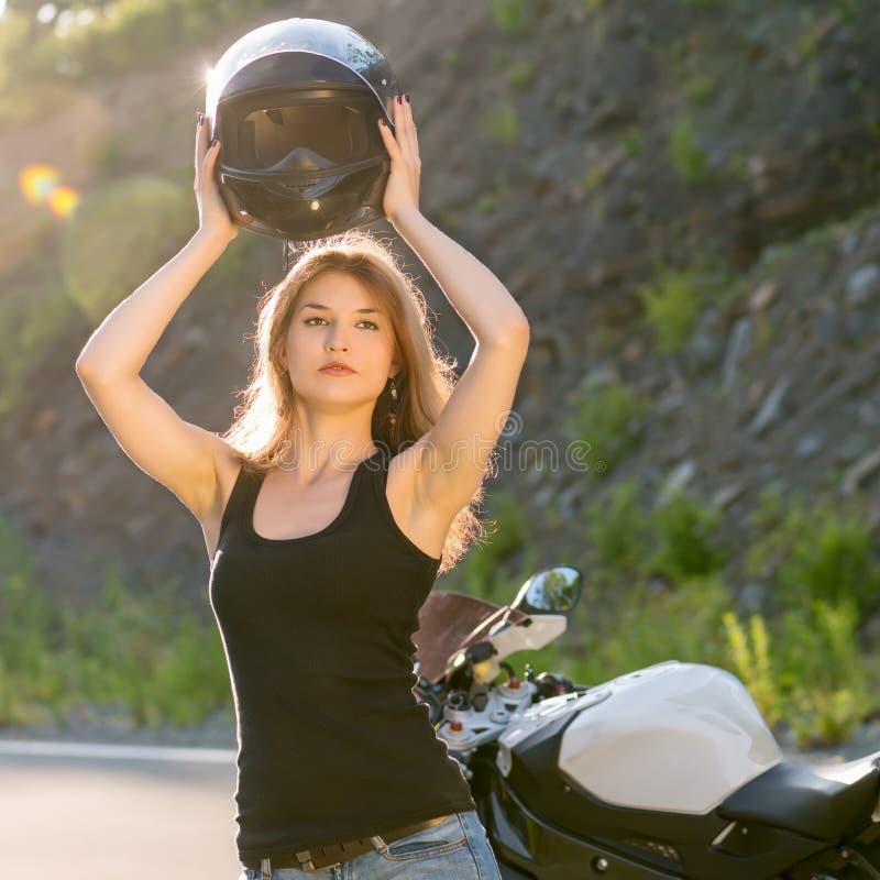 A menina loura remove seu capacete perto da motocicleta fotos de stock