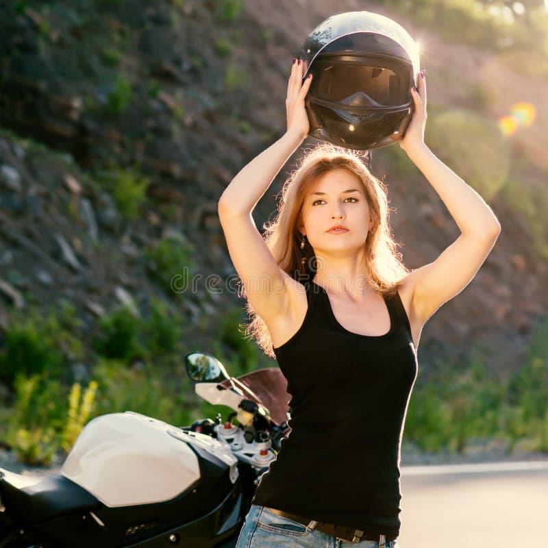 A menina loura remove seu capacete perto da motocicleta fotografia de stock