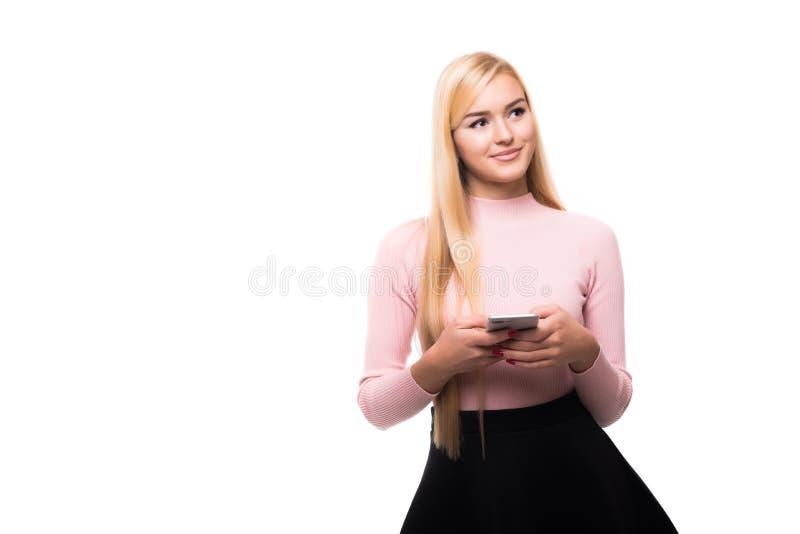 Menina loura satisfeito que usa o smartphone ao texting a mensagem com sorriso Retrato interno da jovem mulher entusiasmado que g imagens de stock royalty free