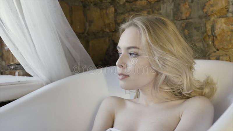 Menina loura sensível com o cabelo encaracolado que senta-se e que olha pensativo em um banho vazio no fundo da parede de tijolo  imagens de stock royalty free