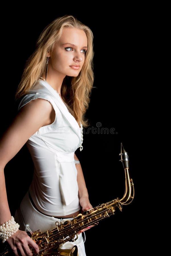 Menina loura sensual nova no vestido branco com saxofone foto de stock