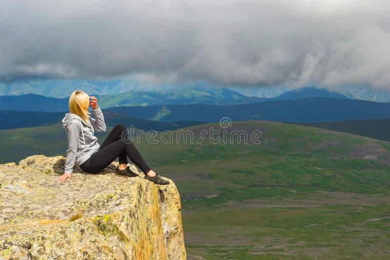 A menina loura senta-se apenas e endireita-se seu cabelo na borda fotos de stock