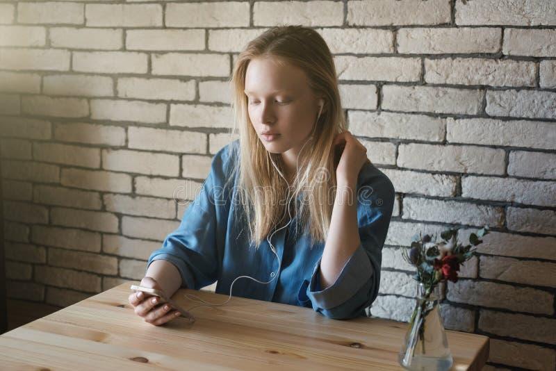 A menina loura senta-se com fones de ouvido e olha-se no telefone que guarda o em uma mão, a outro está endireitando o cabelo foto de stock