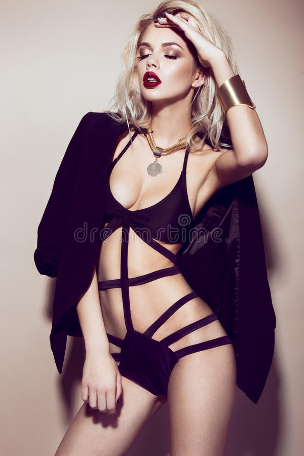 Menina loura 'sexy' bonita com bordos sensuais, cabelo da forma, o vestido preto e os acessórios do ouro Face da beleza foto de stock royalty free