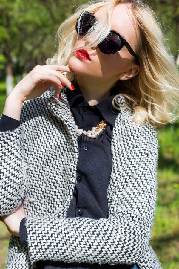 Menina loura 'sexy' bonita com os bordos vermelhos nos óculos de sol que anda no jardim de um dia ensolarado brilhante fotografia de stock