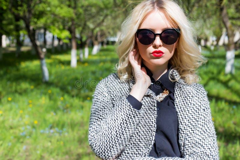 Menina loura 'sexy' bonita com os bordos vermelhos nos óculos de sol que anda no jardim de um dia ensolarado brilhante imagem de stock
