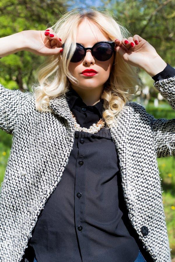 Menina loura 'sexy' bonita com os bordos vermelhos nos óculos de sol que anda no jardim de um dia ensolarado brilhante foto de stock royalty free