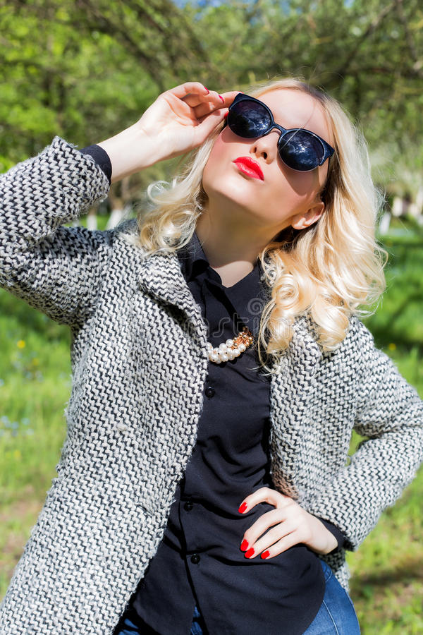 Menina loura 'sexy' bonita com os bordos vermelhos nos óculos de sol que anda no jardim de um dia ensolarado brilhante fotografia de stock royalty free
